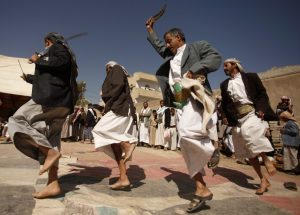 Dancing in Yemen- men in white robes and dark blazers dance with curved knives