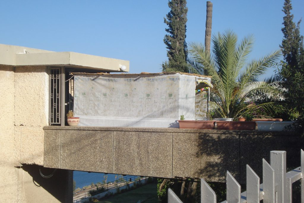 Sukkot in Israel - a white Sukkah on an elevated walkway to someone's front door