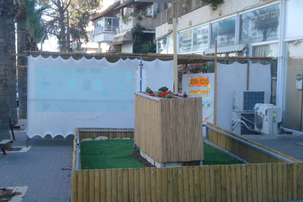 A wooden centerpiece inside a small white Sukkah on the street in Tiberias for Sukkot in Israel